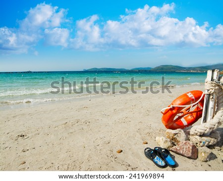 slippers and life buoy by the shore in Alghero, Italy - stock photo