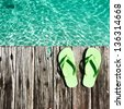 Slippers at jetty by the sea - stock photo