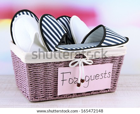 Slippers in basket on table on bright background - stock photo