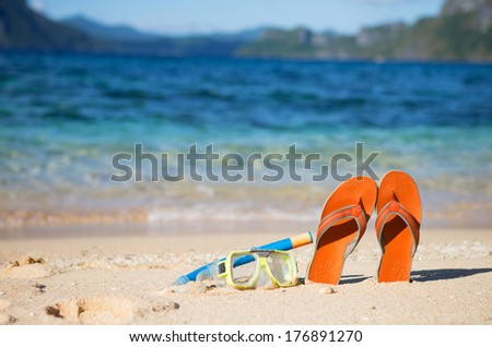 Slippers, mask and snorkel on sand beach near the water - stock photo