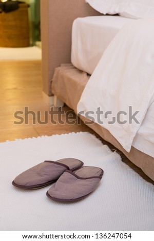 Slippers on the floor of hotel room by the bed - stock photo