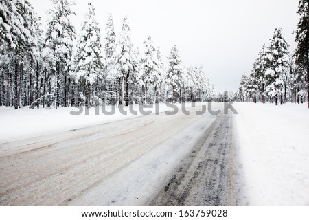 Slippery Winter Road Treated with Sand - stock photo