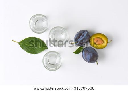 slivovitz (plum brandy) and fresh plums on white background - stock photo