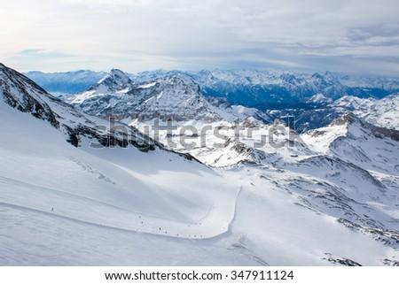 Slope for downhill skiing at Cervinia ski resort in Italian Alps in sunny winter day - stock photo