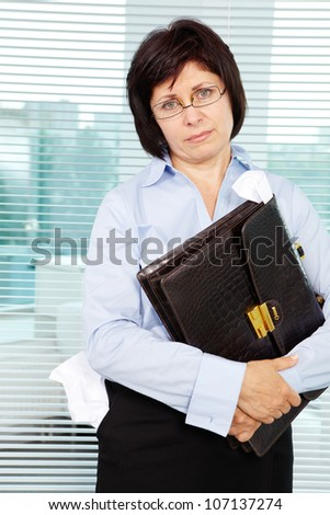Sloppy businesswoman with briefcase looking at camera - stock photo