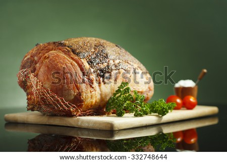 Slow cooked roast beef  covered with mustard sauce, baby tomatoes and garlic sauce on reflective surface and green background - stock photo
