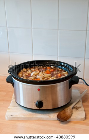 Slow cooker with Lid off and copy space, on a chopping board with wooden spoon - stock photo