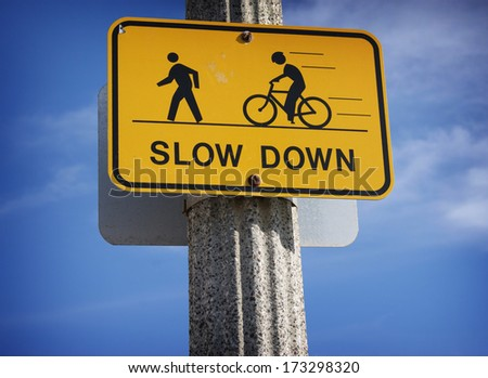 slow down road sign with bicycle - stock photo