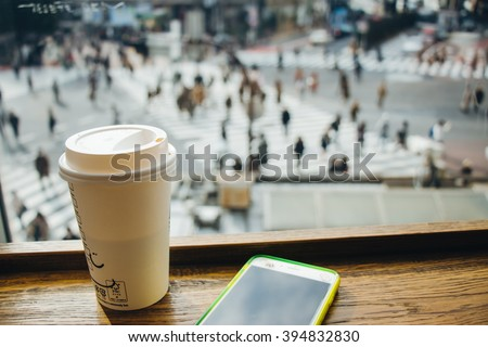 Slow life, Coffee time in rush hour of Big City with blur of people across pedestrian at Shibuya Junction, Tokyo, Japan