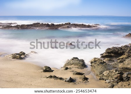Slow motion scenic of a beautiful reef with seawater rushing over a rugged shoreline reef in Laguna Beach, California. - stock photo