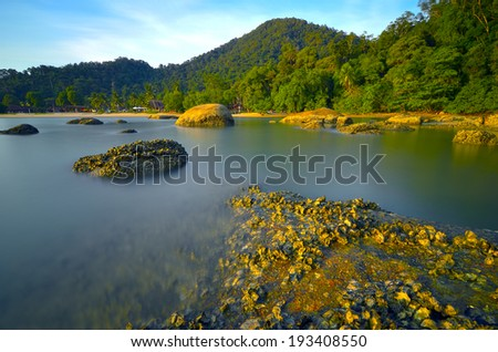 Slow shutter against rocks and blue sky in Pangkor Island, Malaysia - stock photo