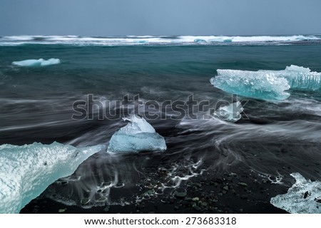Slow shutter photo showing wave movements around Ice blocks that get washed ashore at black sand beach in Iceland during sunset. - stock photo