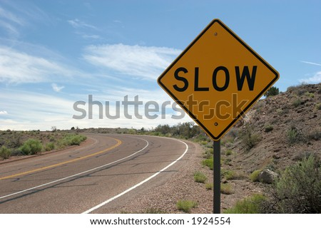 Slow sign and desert road - stock photo