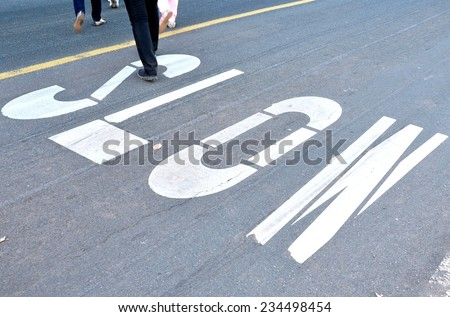 Slow sign painted on the street with pedestrian crossing - stock photo