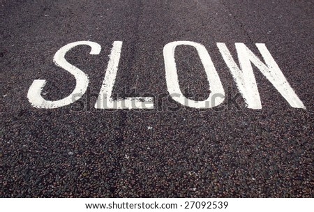 Slow warning sign painted on a street