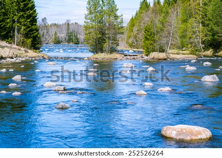 slowly flowing river with plenty of rocks and good fishing spots - stock photo