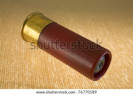 slug in a 12 gauge shotshell on a bright yellow and brown background
