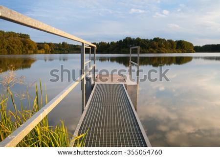 Sluice gate on the pond at sunset - stock photo