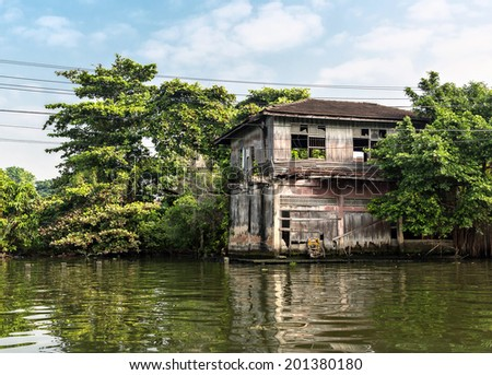 Slum on dirty canal in Thailand - stock photo
