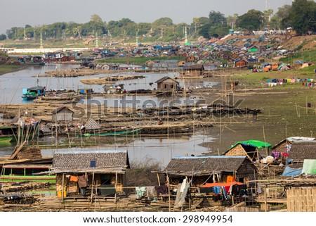 Slum village near the river in the Mandalay city in Myanmar (Burma) - stock photo