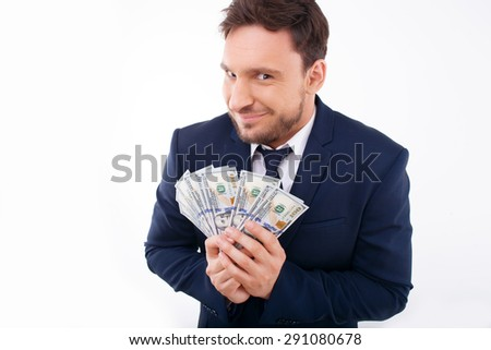 Sly businessman is holding money happily. He is smiling and looking at the camera wilily. Isolated on white background and there is copy space in the left side