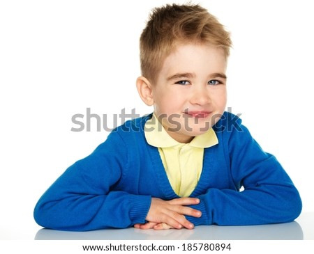 Sly little boy in blue cardigan and yellow shirt