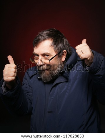 Sly old man in glasses showing yes in a dark background