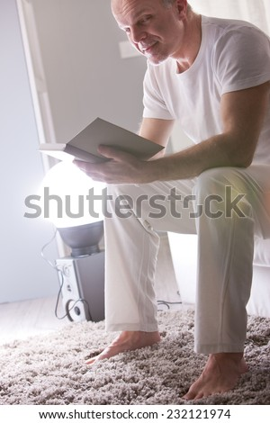 sly smile of a relaxed mature man reading a book at home in a white living room