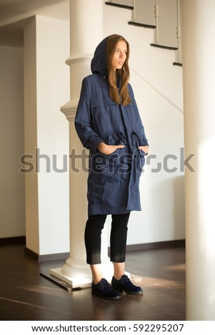 slylish girl in a blue coat with her hands in pockets wearing hood in a minimalistic interior full of sun