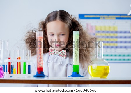 Slyly smiling girl posing with colorful test-tubes - stock photo