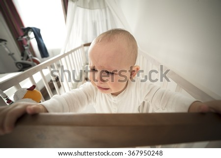 small abandoned baby in the crib crying,