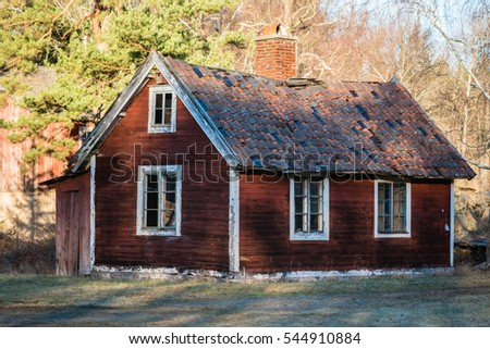 Small abandoned red wooden house with collapsing roof and broken windows.