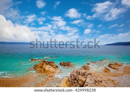 Small Adriatic coastline Croatia. Clear azure water under blue sky. - stock photo