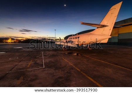 Small aeroplane infront of aircraft hangar during sunrise.