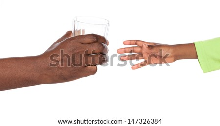 Small african child's hand reaching for a clear glass of water in the hand of an african adult man. Image is isolated on a white background. - stock photo