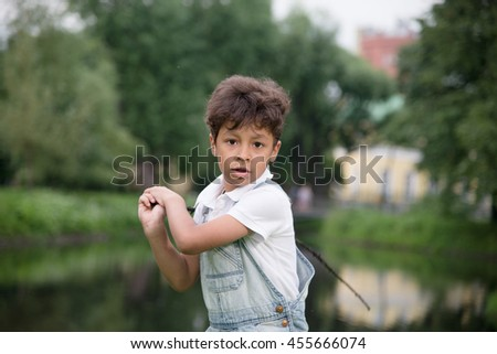 small afro-american boy fooling around the pond