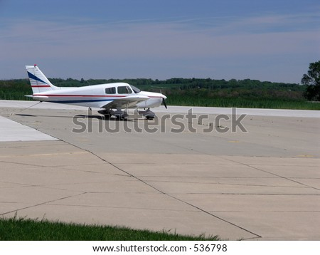 Small aircraft parked after landing at a small rural airport - stock photo