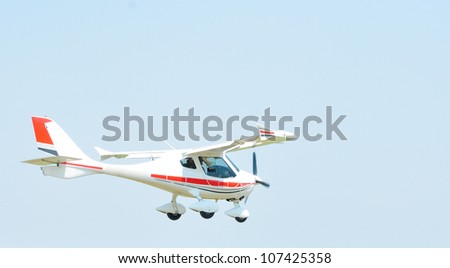 Small airplane flying against blue sky at airshow - stock photo