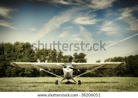 Small airplane parked in a meadow - stock photo