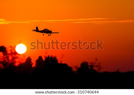 small airplane silhouette against the backdrop of the setting sun - stock photo
