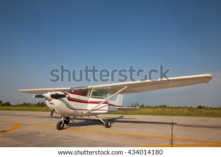 Small airplane with propeller in front parking on runway. - stock photo