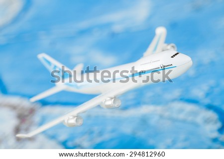 Small airplane with world map on background - stock photo