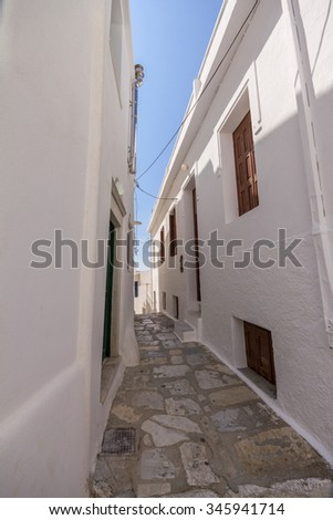 Small alleyway between white houses on the island of Naxos, Greece - stock photo