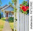 Small American house and white fence with red roses. - stock photo