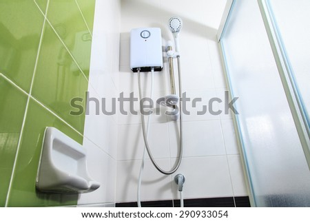 Small and compact bathroom, hot shower and shower head - stock photo