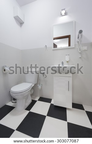 Small and compact bathroom with black and white floor