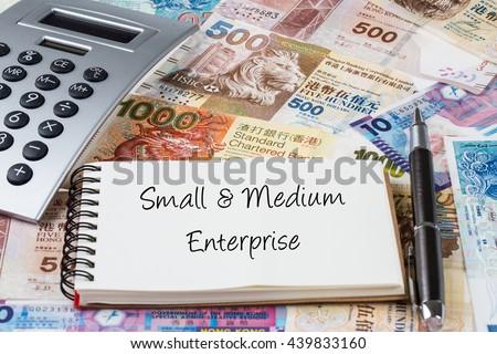 Small and medium enterprise - Stack of Hong Kong dollar or banknotes with handwriting notepad and calculator conceptual - stock photo