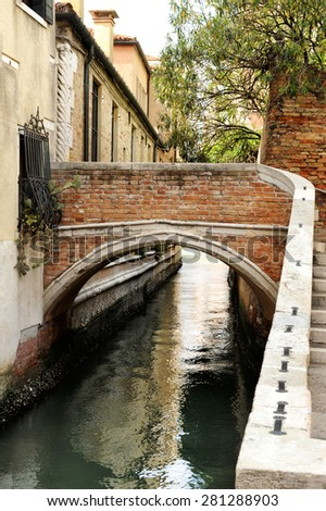 Small Arched Foot Bridge over Narrow Canal Lined with Houses, Venice, Italy