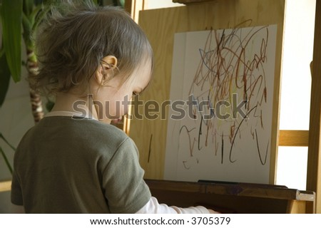 Small artist drawing at a wooden easel. concentrate - stock photo