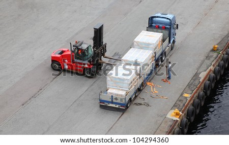 Small auto-loader unload truck, labourer help, view from above - stock photo